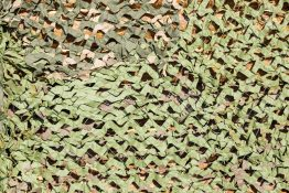the abstract textured camouflage net for masking of green color for a military background